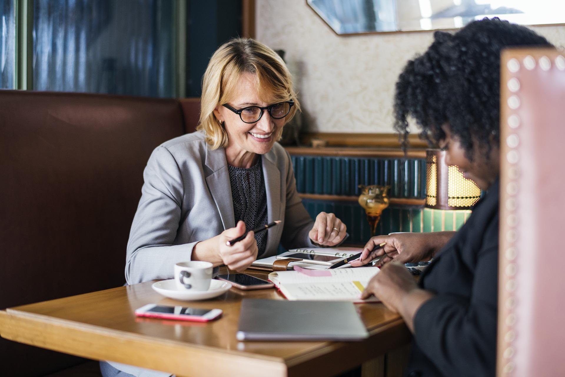 twee vrouwen aan tafel pratend over budgetcoaching